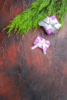Draufsicht weihnachtsgeschenke mit rosa box und weißem band-baumzweig auf dunkelrotem hintergrund