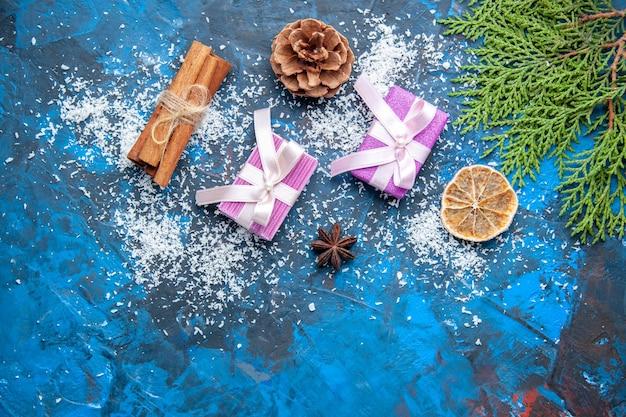 Draufsicht weihnachtsgeschenke tannenbaum zweige kegel anis auf blauem hintergrund