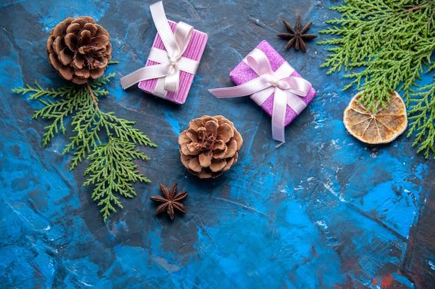 Draufsicht weihnachtsgeschenke tannenbaum zweige kegel anis auf blauer oberfläche