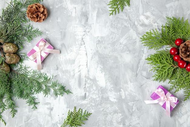 Draufsicht weihnachtsgeschenke weihnachtsbaum spielzeug kiefernzweige auf grauem hintergrund