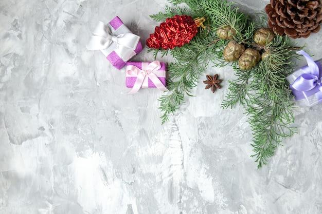 Draufsicht weihnachtsgeschenke weihnachtsbaum spielzeug kiefernzweige auf grauer oberfläche