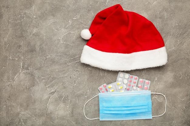 Draufsicht weihnachtsmütze mit medizin und gesichtsmaske