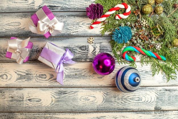 Draufsicht weihnachtsschmuck geschenke süßigkeiten tannenzweige auf holzoberfläche