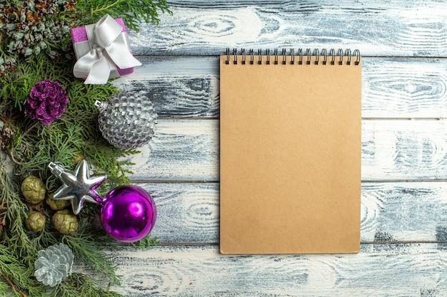 Draufsicht weihnachtsschmuck kleines geschenk tannenbaum zweige weihnachtsspielzeug notebook auf holzoberfläche