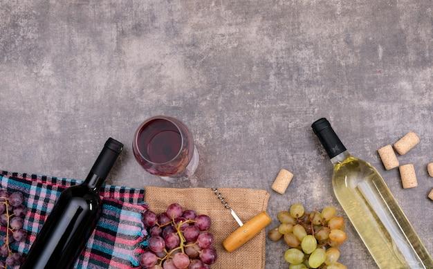Draufsicht weinflaschen mit glas auf sackleinen und kopierraum auf dunklem stein horizontal