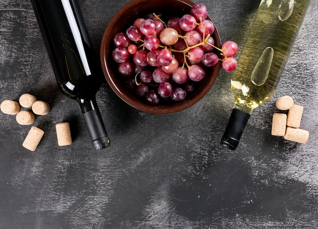 Draufsicht weinflaschen mit trauben- und kopierraum auf schwarzem stein horizontal