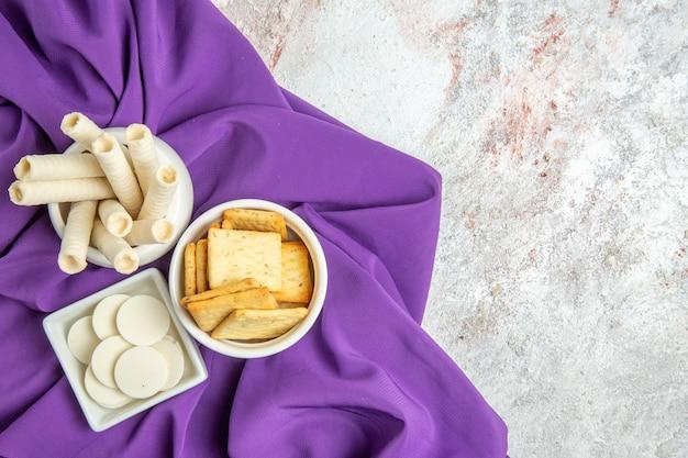Draufsicht weiße bonbons mit crackern auf lila gewebefarbe bonbon süß