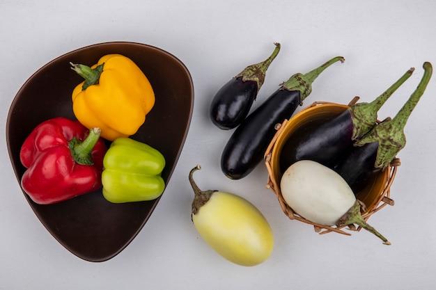 Draufsicht weiße und schwarze auberginen in einem korb mit farbigem paprika in einer schüssel auf weißem hintergrund