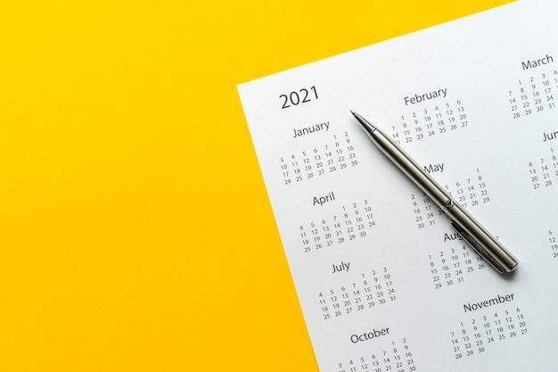 Draufsicht weißer kalender 2021 zeitplan mit stift auf gelbem farbhintergrund