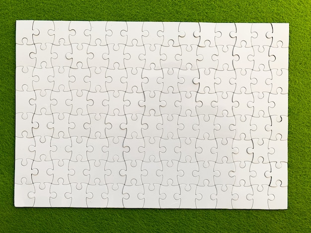 Draufsicht, weißes puzzlespiel auf grün