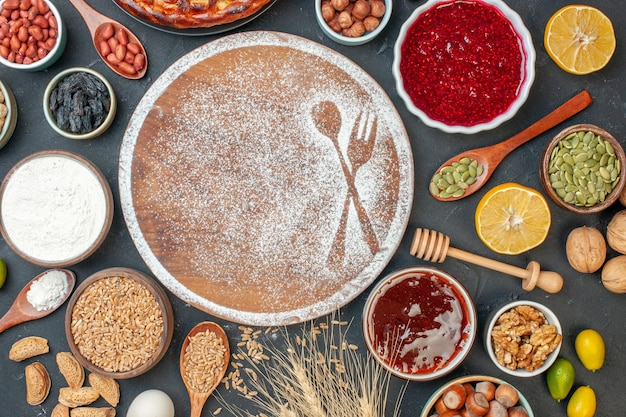 Draufsicht weißmehl in gabel- und löffelform mit eiern und nüssen auf dunklem kuchen süßer tee dessert keks gebäck pie