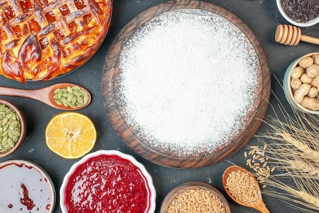 Draufsicht weißmehl mit frischen samen und marmelade auf einem dunklen fruchtsüßkuchen zuckerkuchen teegebäck dessertkeks