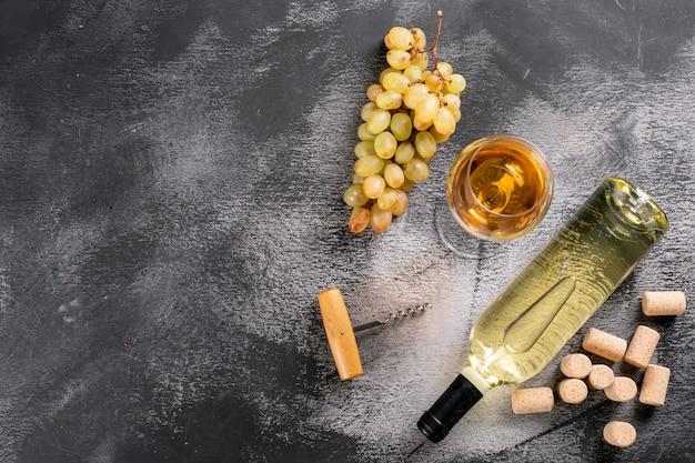Draufsicht weißwein mit trauben- und kopierraum auf schwarzem stein horizontal