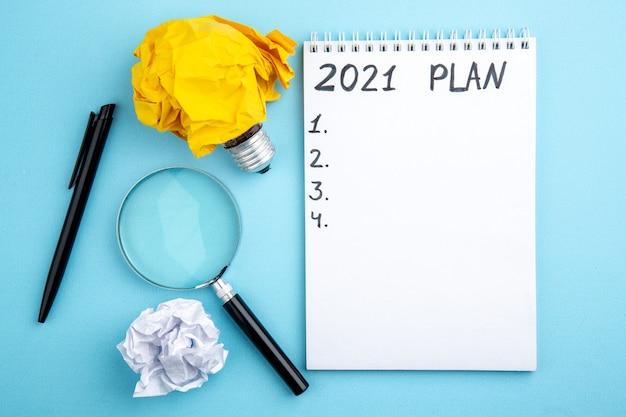 Draufsicht zerknittertes papier mit idee glühbirne konzept lupa stift plan auf notizblock auf blauem hintergrund geschrieben