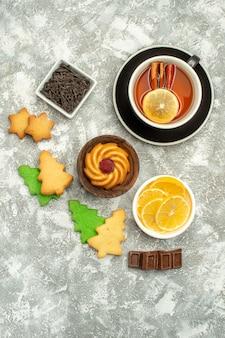 Draufsicht zimt zitronen tee kekse schalen mit schokolade und zitronenscheiben auf grauer oberfläche