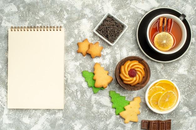 Draufsicht zimt zitronen tee kekse schalen mit schokolade und zitronenscheiben notizbuch auf grauer oberfläche