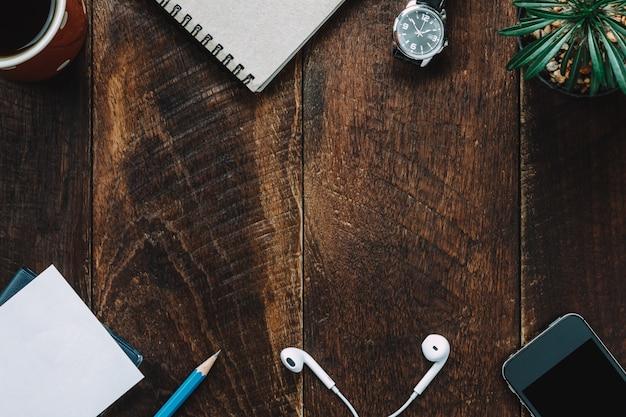 Draufsicht zubehör büro schreibtisch der handy, tag, bleistift, notizpapier, kaffee, kaktus, kopfhörer auf hölzernen büro schreibtisch hintergrund.