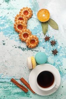 Draufsicht zuckerkekse mit macarons und tasse tee auf blauer oberfläche