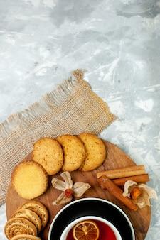 Draufsicht zuckerplätzchen mit tasse tee auf weißem schreibtischplätzchenkeks süßer kuchenkuchen