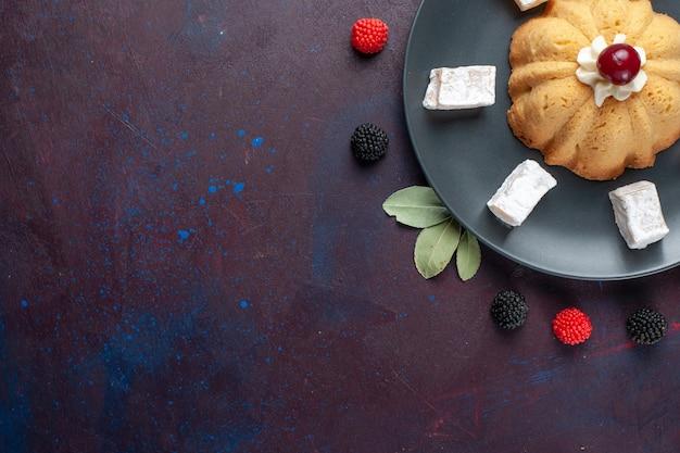 Draufsicht zuckerpulverbonbons köstliches nougat mit kuchen und konfektionsbeeren auf dunkler oberfläche