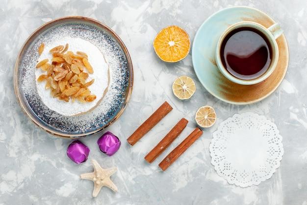 Draufsicht zuckerpulverisierte rosinen getrocknete trauben auf kleinem kuchen mit tee und zimt auf weißem schreibtisch