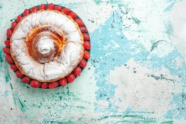 Draufsicht zuckerpulverkuchen mit frischen roten erdbeeren auf der hellblauen oberfläche