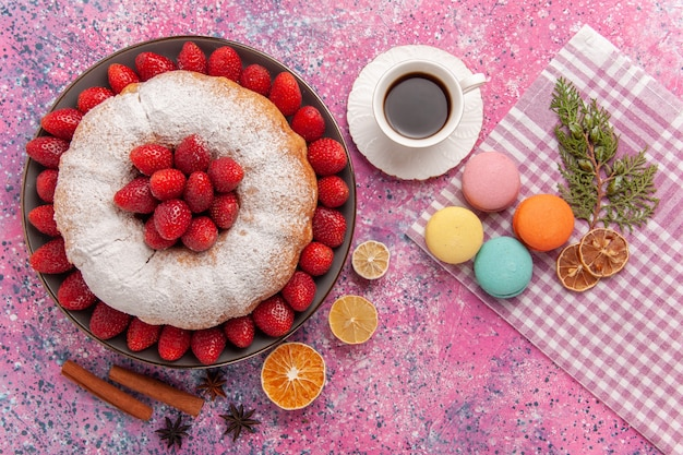 Draufsicht zuckerpulverpastete erdbeerkuchen mit macarons auf hellrosa