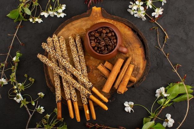 Draufsicht zuckerstangen zusammen mit zimt und braunen kaffeesamen auf dem dunklen boden
