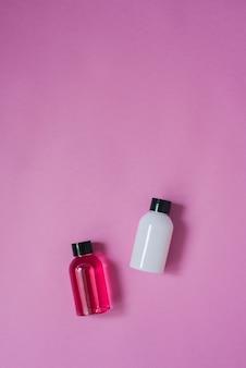 Draufsicht zusammensetzung der kleinen reiseflaschen für kosmetik, duschgel, shampoo und haarbalsam auf einem rosa tisch. konzept der körper- oder haarpflege mit kopierraum.