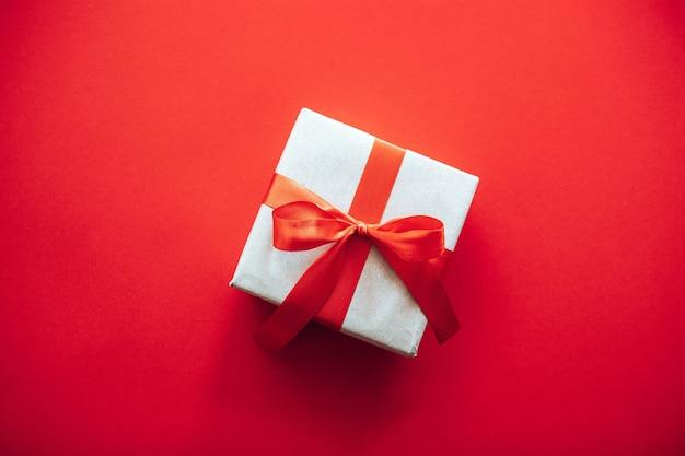 Draufsicht zusammensetzung der weihnachtsgeschenkbox eingewickelt in bastelpapier mit roter schleife