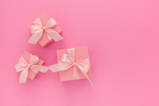 Draufsicht zusammensetzung: drei rosa geschenkboxen mit band