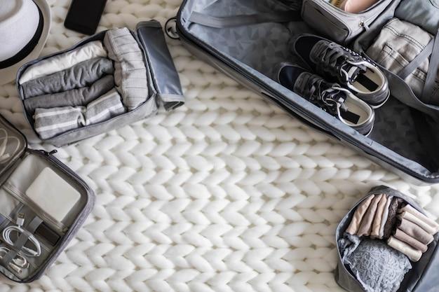 Draufsicht-zusammensetzung mit ordentlich verpackten sachen, kleidung und accessoires für die reise-konmari-methode