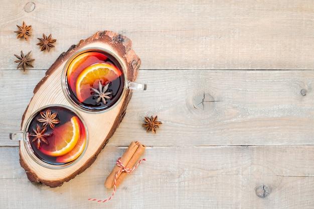 Draufsicht zwei gläser glühwein mit gewürzen und orangenscheiben auf einem hölzernen hintergrund