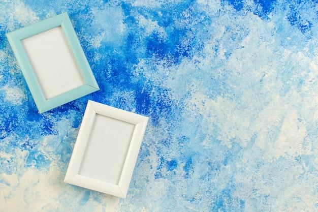 Draufsicht zwei leere bilderrahmen auf blauem weißem schmutz mit freiem speicherplatz