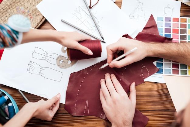 Draufsicht zwei modedesigner, die ausschnitt machen.