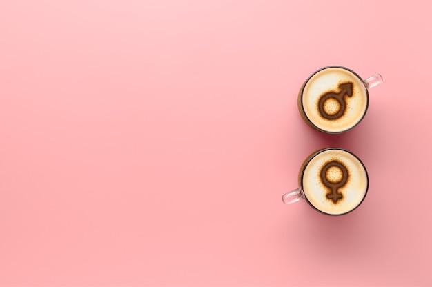 Draufsicht zwei tassen kaffee mit symbolen der venus und des mars auf geschlagenem milchschaum. pastellrosa hintergrund. konzept romantisches datum am valentinstag. kreative flache lage, kopierraum