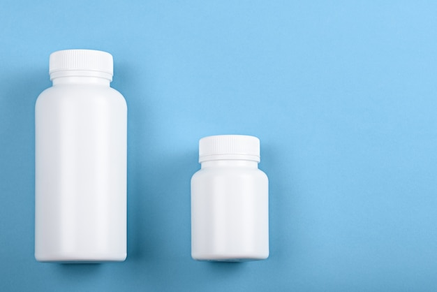 Draufsicht zwei weiße plastikflaschen auf blauem hintergrund für marke