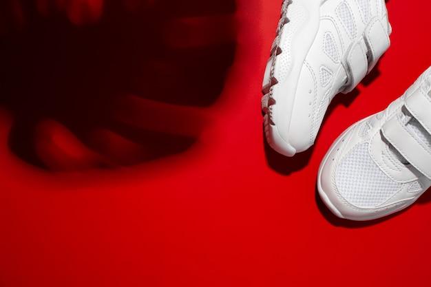 Draufsicht zwei weiße unisex-sneaker mit harten schatten aus dem monstera-blatt isoliert auf einem roten, lebendigen ...