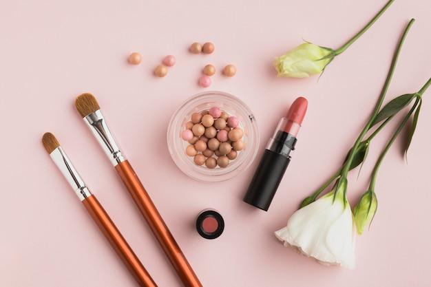 Draufsichtanordnung mit kosmetischen produkten und rosa hintergrund