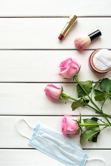 Draufsichtanordnung mit make-up, rosen, medizinischer maske und kopienraum auf weißem hölzernem hintergrund. konzept der schönheit in der covid-19-ära.