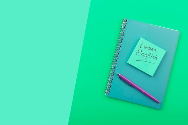 Draufsichtanordnung mit notizbuch auf grünem hintergrund