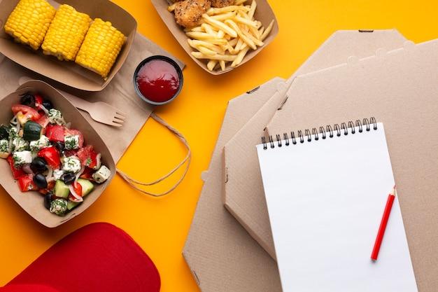 Draufsichtanordnung mit notizbuch auf pizzakästen