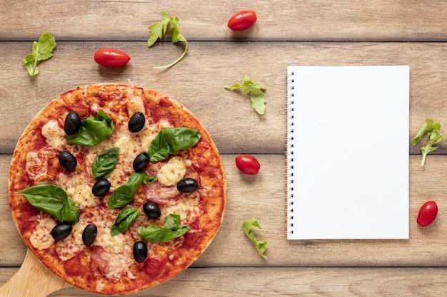 Draufsichtanordnung mit pizza und notizbuch