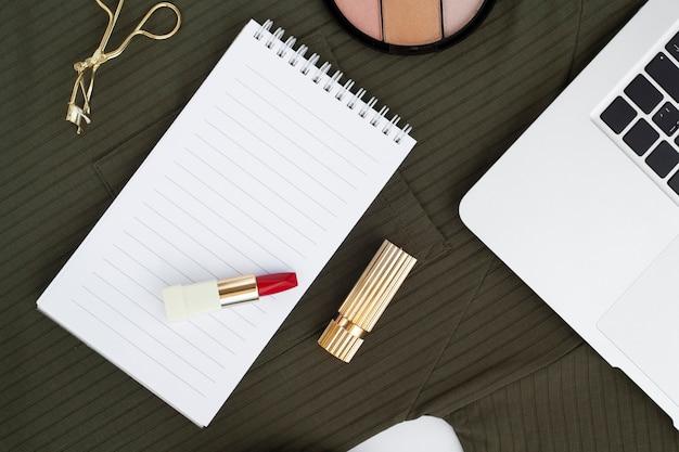 Draufsichtanordnung mit rotem lippenstift auf notizbuch