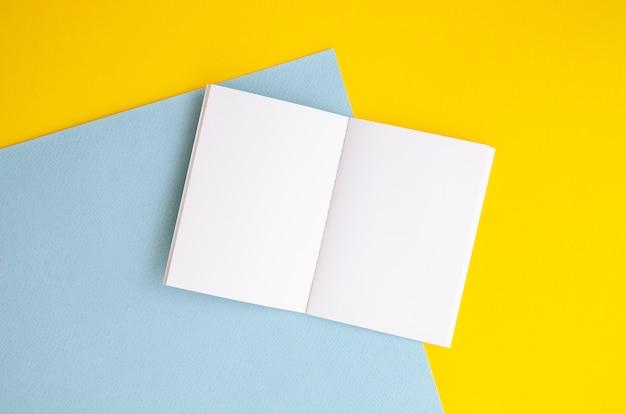 Draufsichtanordnung mit weißem notizbuch und buntem hintergrund