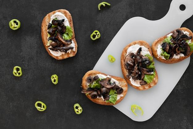 Draufsichtanordnung von köstlichen sandwiches auf schwarzem hintergrund