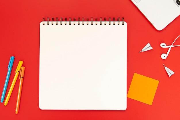 Draufsichtanordnung von schreibtischelementen auf rotem hintergrund