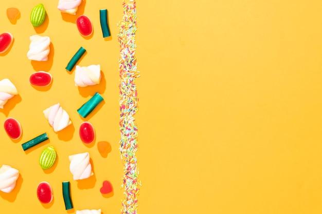 Draufsichtanordnung von verschiedenfarbigen bonbons auf gelbem hintergrund mit kopienraum