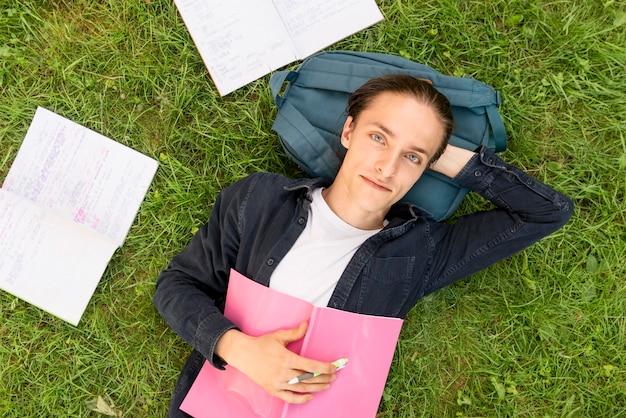 Draufsichtansicht junger student, der sich auf dem campus entspannt