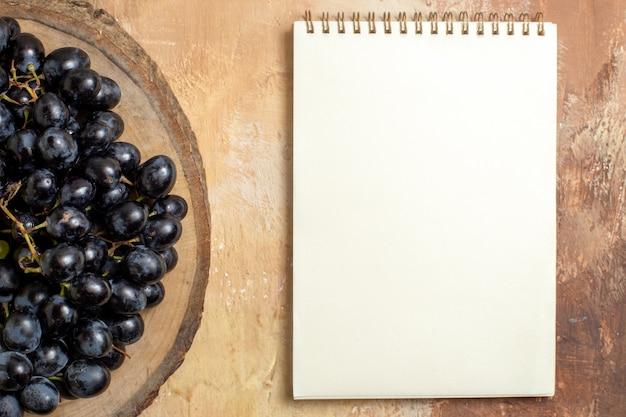 Draufsichtansicht weintrauben der schwarzen trauben auf dem weißen notizbuch des hölzernen schneidebretts